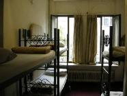 Viengulė lova vyrų nakvynės namų kambaryje