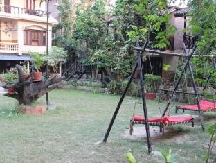 Hotel River Side Chitwan - Old building with hammocks in the garden